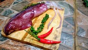 Calamaro fresco con Libro Verde ed i peperoncini rossi su legno Fotografia Stock Libera da Diritti