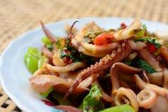 Calamaro in padella e basilico sul baske bianco del bambù della sfuocatura e del piatto Immagine Stock Libera da Diritti