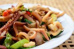 Calamaro in padella e basilico sul canestro bianco del bambù della sfuocatura e del piatto Fotografia Stock Libera da Diritti