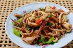 Calamaro in padella e basilico sul canestro bianco del bambù della sfuocatura e del piatto Fotografia Stock