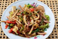 Calamaro in padella e basilico sul canestro bianco del bambù della sfuocatura e del piatto Immagine Stock