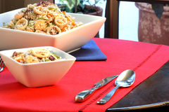 Calamary rice. Delicious calamary rice with assorted seafood and vegetables served on nice fancy table Stock Photos