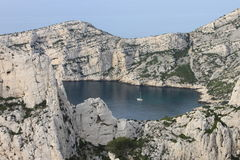 Calanques gulf in Marseilles. A blue lake inside rocks included a little boat in the middle, where outside is the Mediterranean sea. seems like two world put Stock Photos