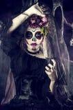Female skeleton face. Calavera Catrina in black dress over dark background. Sugar skull makeup. Dia de los muertos. Day of The Dead. Halloween royalty free stock photo