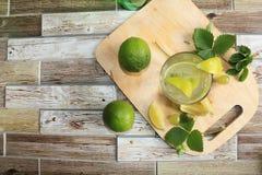 Calce in calici e frutta di vetro con la menta su una tavola di legno immagine stock libera da diritti