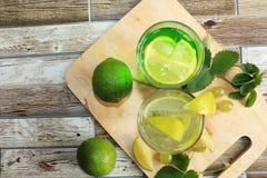 Calce in calici e frutta di vetro con la menta su una tavola di legno immagini stock