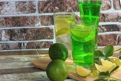 Calce in calici e frutta di vetro con la menta su una tavola di legno immagini stock libere da diritti