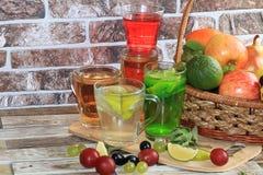 Calce in calici e frutta di vetro con la menta su una tavola di legno fotografia stock libera da diritti