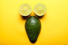 Calce ed avocado affettati su fondo giallo Fotografia Stock
