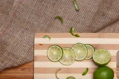 Calce verde fresca con le fette sul bordo di bambù di legno della cucina Fotografie Stock