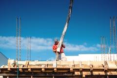 Calcestruzzo di versamento del lavoratore durante il cantiere immagine stock