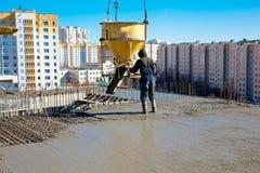 Calcestruzzo di versamento dell'operaio di costruzione Immagini Stock