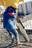 Calcestruzzo di versamento dell'operaio di costruzione Fotografia Stock