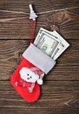 Calcetín de la Navidad con los dólares del regalo Foto de archivo libre de regalías