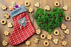 Calcetín de la Navidad con los regalos y el fondo de la panadería con las galletas y Fotos de archivo libres de regalías
