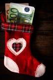 Calcetín de la Navidad relleno con el dinero Imagen de archivo