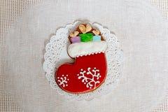 Calcetín del pan de jengibre de la Navidad con los regalos en un fondo de la servilleta Galleta del pan de jengibre de la media d Imágenes de archivo libres de regalías