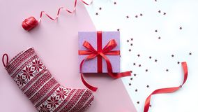 Calcetín rojo de la Navidad con el regalo en el fondo del rosa y blanco fotos de archivo