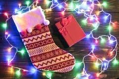 Calcetín rojo de la Navidad y guirnalda brillante Foto de archivo libre de regalías
