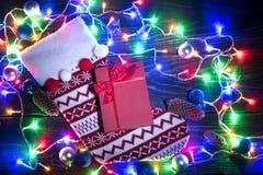 Calcetín rojo de la Navidad y guirnalda brillante Fotografía de archivo libre de regalías