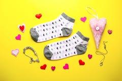 Calcetines, accesorios de la joyería y corazones femeninos en backgroun amarillo Fotos de archivo libres de regalías