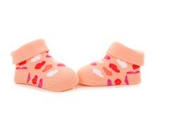Calcetines anaranjados rosados del bebé con los corazones en un backgroun blanco Imagen de archivo