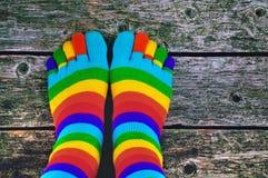 Calcetines coloreados con los dedos del pie en un fondo de madera Fotografía de archivo libre de regalías