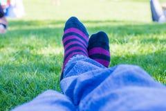 Calcetines coloreados de un adolescente que está descansando en un parque Imagen de archivo libre de regalías