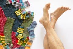 Calcetines de lana coloridos y un par de piernas en el fondo blanco fotografía de archivo