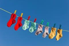 Calcetines del bebé en la línea del lavadero a secarse fotos de archivo