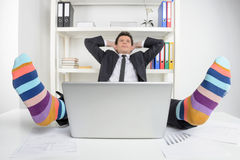 Calcetines enrrollados. Hombre de negocios feliz en los calcetines enrrollados que se sientan en su wor Fotos de archivo