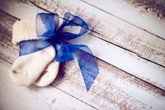 Calcetines hechos punto del bebé con la cinta azul en la superficie de madera Imagenes de archivo