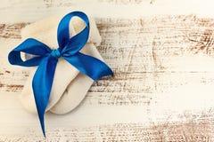 Calcetines hechos punto del bebé con la cinta azul en la superficie de madera Imagen de archivo