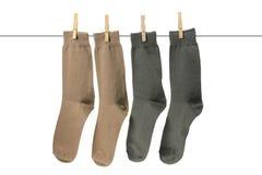 Calcetines que cuelgan en cuerda para tender la ropa Fotos de archivo