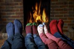 Calcetines que llevan de la familia que calientan pies por el fuego imagen de archivo