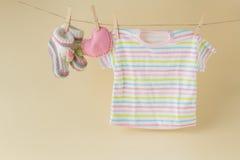 Calcetines y ropa del bebé que cuelgan en la cuerda para tender la ropa Foto de archivo