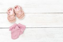 Calcetines y zapatos rosados para la niña en un backgroun de madera blanco Foto de archivo libre de regalías