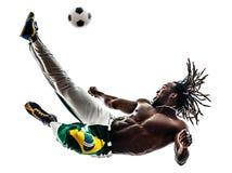Calciatore brasiliano dell'uomo di colore che dà dei calci alla siluetta di calcio Immagine Stock
