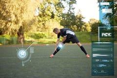 Calciatore che allunga gamba su calcio del campo Fotografie Stock