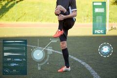 Calciatore che allunga gamba su calcio del campo Immagini Stock