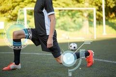 Calciatore che allunga gamba su calcio del campo Immagine Stock