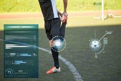 Calciatore che allunga gamba su calcio del campo Fotografie Stock Libere da Diritti