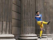 Calciatore che dà dei calci alla palla fra le colonne Fotografia Stock Libera da Diritti