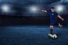 Calciatore che dà dei calci alla palla in un grande stadio la notte Fotografia Stock Libera da Diritti