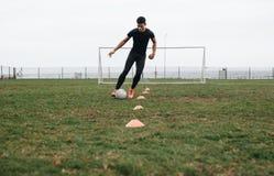 Calciatore che fa il trapano di gocciolamento del cono sul campo Calciatore che muove la palla fra i coni che praticano gocciolam fotografie stock libere da diritti