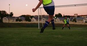 Calciatore femminile che segna scopo mentre il custode prova a prenderlo sul campo di calcio 4K video d archivio