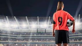Calciatore femminile che sta con la palla contro lo stadio ammucchiato alla notte immagine stock