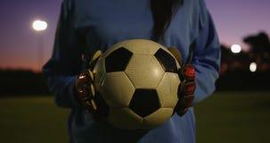 Calciatore femminile che tiene la palla sul campo di calcio 4K archivi video