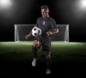 Calciatore ispano che gioca a calcio su un fondo scuro fotografia stock libera da diritti