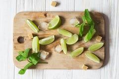 Calcini le fette, il ghiaccio, la menta ed i cubi di zucchero bruno Ingredienti per Immagine Stock